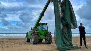 tractor lifting fishing net on beach