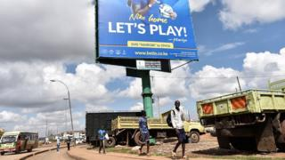 Boys walk under a billboard advertising a popular sports betting site in Nairobi