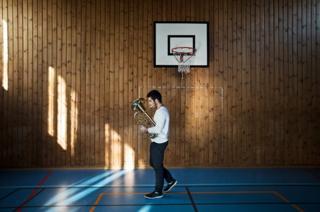 A boy practices his trombone