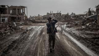 مقاتل يسير وسط منازل مدمرة في سوريا