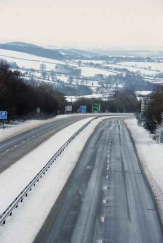 The A30 road seen empty with snow-covered hills seen in the background