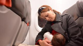 A woman breastfeeds her baby on an aeroplane