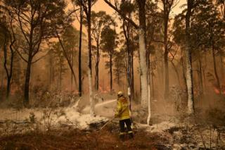 A firefighter sprays foam retardant