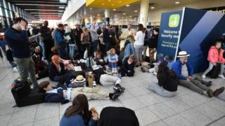 Passengers wait at the North Terminal at London Gatwick Airport, south of London, on December 20, 2018 after all flights were grounded due to drones flying over the airfield