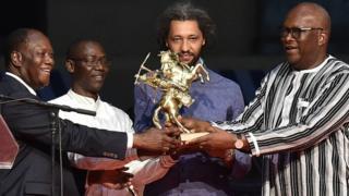 Le réalisateur franco-sénégalais, Alain Gomis, reçoit l'Etalon d'Or du Yennenga des mains des présidents Roch Marc Christian Kabore (droite) du Burkina Faso et Alassane Dramane Ouattara (gauche) de Côte d'Ivoire