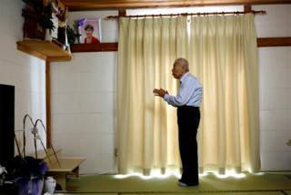 Ryuichi Nagayama prays at an altar at his home