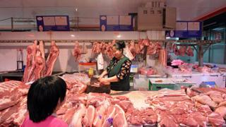 Chinese butcher preparing slabs of pork for sale at a market in Beijing