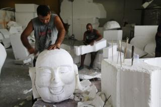 Workers at the Mangueira samba school carve figures out of polystyrene