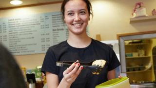 Woman putting food in tupperware