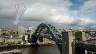 The Red Arrows display team soar over the Tyne Bridge as thousands of runners cross it