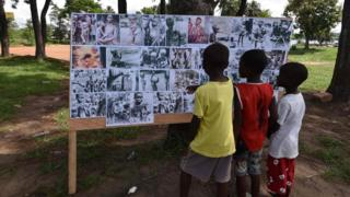 Children look at a placard on May 30, 2017 in Abidjan, during commemorations of the 50th anniversary of the Nigerian civil war. Nigeria on May 30 marks 50 years since the declaration of an independent Republic of Biafra plunged the country into a civil war, amid renewed tensions and fresh calls for a separate state. The main pro-independence groups - the Indigenous People of Biafra (IPOB), and the Movement for the Actualisation of the Sovereign State of Biafra (MASSOB) - have called for a day of reflection.