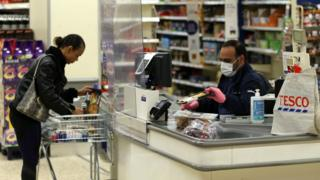 A Tesco supermarket cashier wearing protective face mask and gloves assists a shopper behind a plastic screen