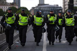 Police officers runs across Waterloo Bridge to reinforce colleagues on the Strand after protesters supporting the Black Lives Matter movement clash with opponents in central London