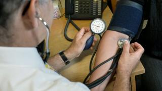 A doctor takes a patient's blood pressure