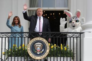 US President Donald Trump and first lady Melania Trump wave beside a person in an Easter Bunny costume on the Truman balcony of the White House