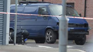 A bomb disposal expert examines the prison officer's van after the explosion in Hillsborough Drive, east Belfast