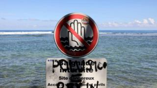 A file photo taken on 25 February, 2010, shows a sign banning swimming at Saint-Leu, on the Indian Ocean island of Reunion