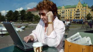 A woman talks on a phone and works on a laptop outside in Helsinki
