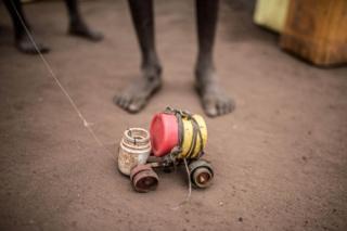 A boy plays with a toy car in Rhino refugee camp in northern Uganda