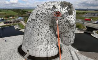 Men on crane next to Kelpies