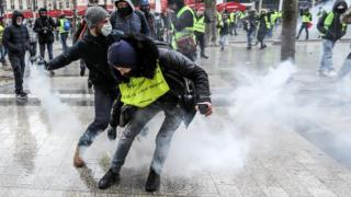 Protesters wearing yellow vests (gilets jaunes) clash with French riot police during a demonstration on the Champs-Elysées in Paris on December 15.