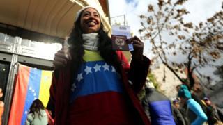 Mujer muestra su pasaporte después de votar.