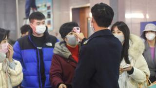 Passengers in Hangzhou, China are screened with temperature checks after arriving from Wuhan