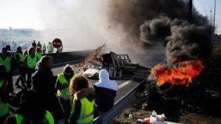 French protesters stand near a fire and blockade in western France