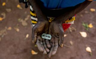 "An FGM ""cutter"" in Kenya shows the razorblade she uses to cut girls' genitals"