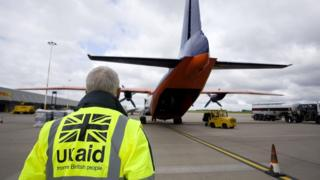sports A Dfid employee wearing a UK aid hi-vis heads towards a plane