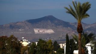 Bandeira da República Turca de Chipre do Norte pintada em uma montanha na cidade de Nicósia, capital do país - dividida ao meio pela Linha Verde