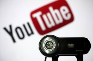 A webcam is positioned in front of a YouTube logo