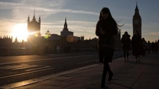 A woman walks across Westminster Bridge