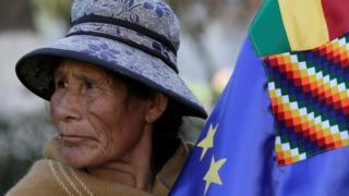 Una mujer sostiene la bandera marítima de Bolivia.