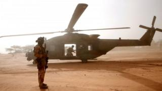 A French soldier stands in front of military helicopter in Mali