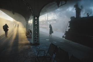 Passengers stand on a train platform in the early morning