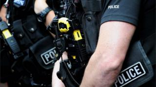 Close up picture of an officer carrying a Taser