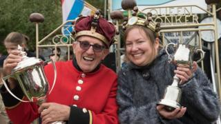A Chelsea Pensioner and a woman, both wearing crowns decorated with conkers, hold their trophies aloft sitting in chairs that say 'King Conker' and 'Queen Conker'.
