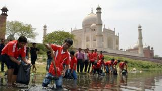 Students from the Institute of Hotel and Tourism pose as they participate in a clean-up of the Yamuna River at Dussehra Ghat behind the Taj Mahal in Agra on April 18, 2012.