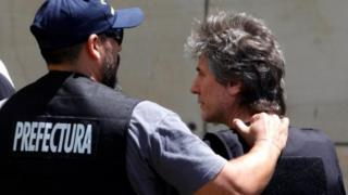 """Former Argentine Vice President Amado Boudou is escorted by a member of Argentina""""s Coastguards as he arrives to a Federal Justice building in Buenos Aires, Argentina November 3, 2017. REUTERS"""