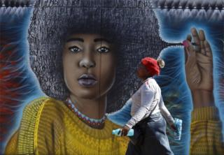 A woman walks past a spray-painted mural depicting a woman with an afro.