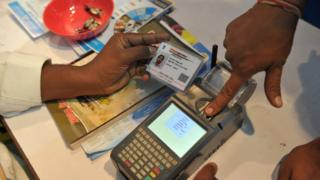 An Indian visitor gives a thumb impression to withdraw money from his bank account with his Aadhaar card.
