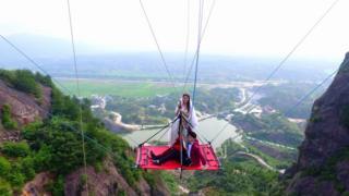 The couple suspended off Shiniuzhai glass bridge, 9 August 2016