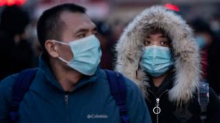 Chinese citizens wearing protective masks board trains in Beijing, 21 January 2020