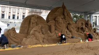 Russian artist Ilya Filimontsev (L) and Czech artist Radovan Zivny (R) sculpt sand to construct a nativity scene at Piazza San Pietro in The Vatican on 6 December 2018