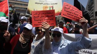 """تصویری از اعتراض فلسطینیها در کرانه غربی رود اردن. بر روی پلاکارد معترضین فلسطینی نوشته شده است: """"معامله ترامپ هرگز تصویب نمیشود. فلسطین برای فروش نیست."""""""