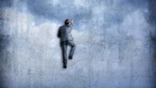 Homem de terno escalando parede
