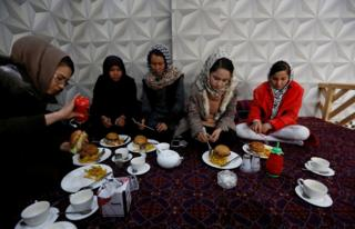 Sima Azimi (left), a trainer at the Shaolin Wushu club, eats lunch with her students at a restaurant in Kabul, Afghanistan