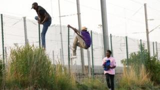 Migrants climb over a fence in Coquelles near Calais