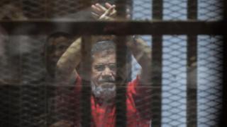 الرئيس المصري السابق محمد مرسي بالزي الاحمر في قفص الاتهام
